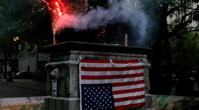 Videos capture Portland rioters bent on burning police precincts coming for neighborhoods, setting dumpster fires. One US flag-caped woman intervenes.