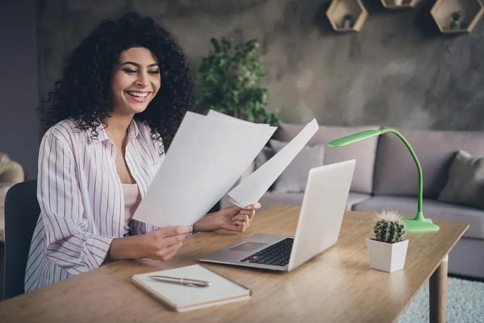 अपना रिज्यूमे और कवर लेटर पढ़ती महिला मुस्कुराती है
