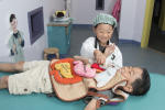 Children playing dress-up as doctor and patient