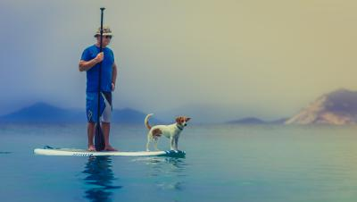 Man and dog standing on a paddle board in a SLO CAL Bay