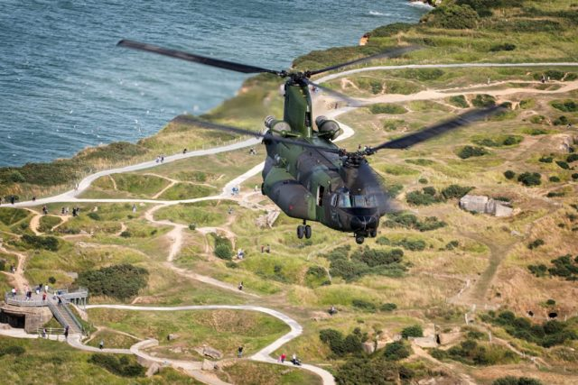 The RCAF CH-147F Chinook flies over the English countryside as observers walk on winding paths below.