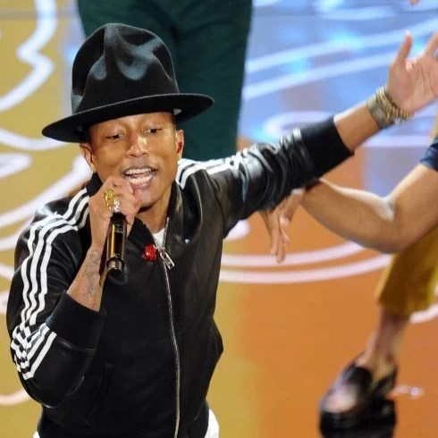 Pharrell Williams wearing a hat and speaking into a mic