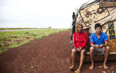 A Guarani-Kaiowa couple sit outside their makeshift roadside settlement of the Apy Ka'y community, near Dourados, Mato Grosso do Sul, Brazil.
