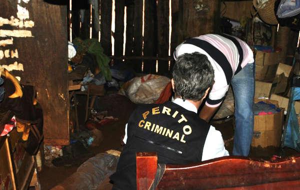 """""""Agentes de policía examinan el cuerpo sin vida de Ambrósio dentro de su cabaña."""""""