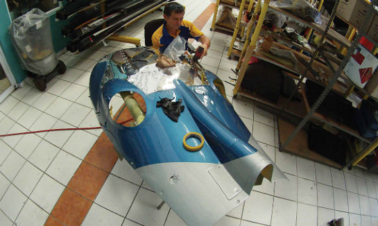 Carlos Negron puts the finishing touches on a modification for a Leonardo Helicopters AW109C rear cowling, designed to eliminate problematic paint and structural damage caused by the aircraft's hot exhaust.