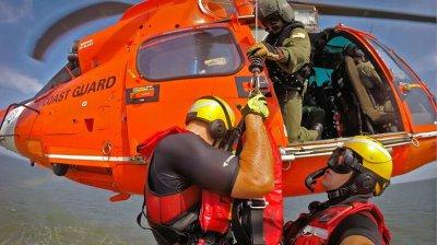A U.S. Coast Guard crew conducting a training hoist on an MH-65 Dolphin.