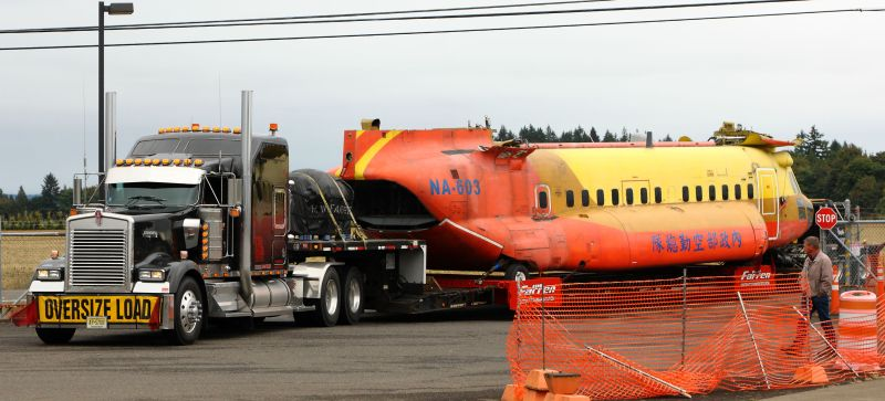 Boeing Model 234 Chinook helicopter rests on the bed of a truck.
