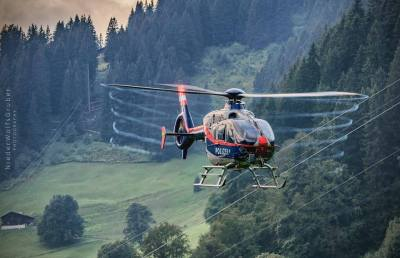 Austrian Police Air Support flying through a lush locale.