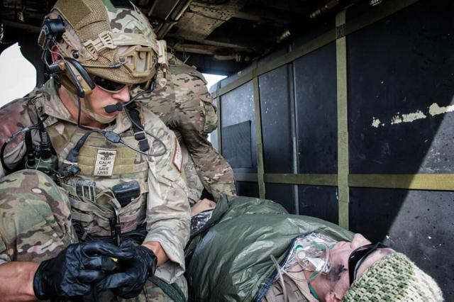 A 57th RQS pararescueman works on a simulated casualty in the back of a HH-60G Pave Hawk.
