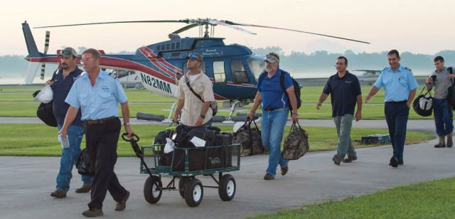 Pilot Doug Greenwald escorts his passengers to the aircraft for a morning flight from the Abbeville base. This facility handles the majority of the company's crew shuttles to and from offshore platforms.