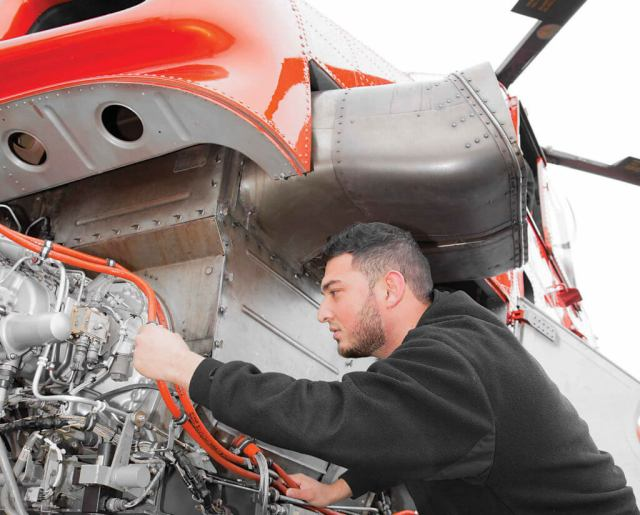 The S-58's engine is mounted in the aircraft's nose. Here, aircraft maintenance engineer Rahmatullah Rahimi takes a look behind the cowlings.