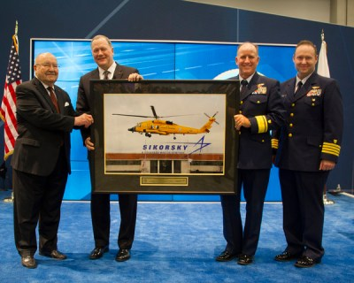 Sergei Sikorsky, left, and Sikorsky president Dan Schultz present U.S. Coast Guard aviators Rear Adm David Callahan and Capt Joe Kimball with a framed photo of an MH-60T Jayhawk helicopter taking off from Sikorsky's Stratford, Connecticut, headquarters on Dec. 7, 2016. The aircraft is painted chrome yellow to commemorate the U.S. Coast Guard's aviation centennial