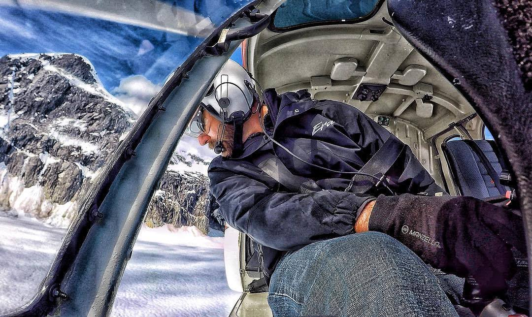 A pilot carefully peers out of the cockpit, with snow-dusted mountains in the background. Photo submitted by Instagram user @jeremy_adventures