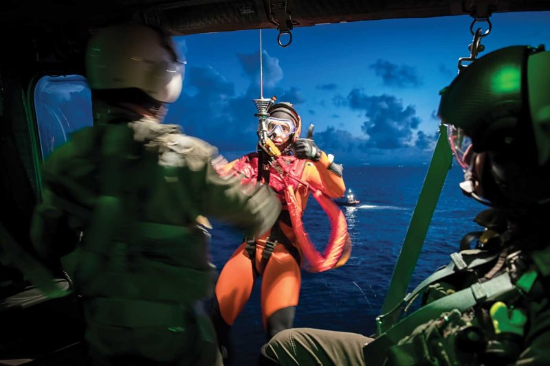 A rescue swimmer gives the thumbs up to the winch operator during a training exercise off the coast of Catania, Sicily, the home of Guardia Costiera's 2° Nucleo Aereo.