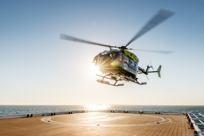 Aerios Global's newest aircraft, the EC145, hovering over a helipad by the water