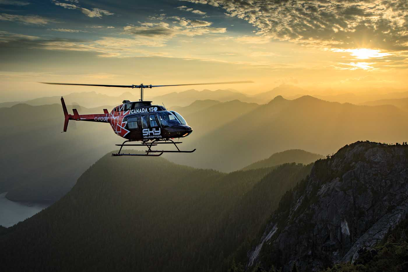 Sky Helicopters' Bell 206L LongRanger holds a hover as the sun sets over some beautiful backcountry near Vancouver, British Columbia. Heath Moffatt Photo