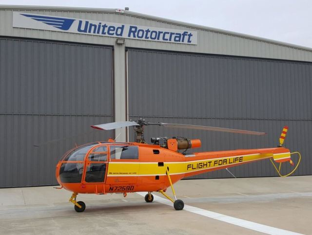 Orange-and-yellow Alouette III in front of United Rotorcraft hangar
