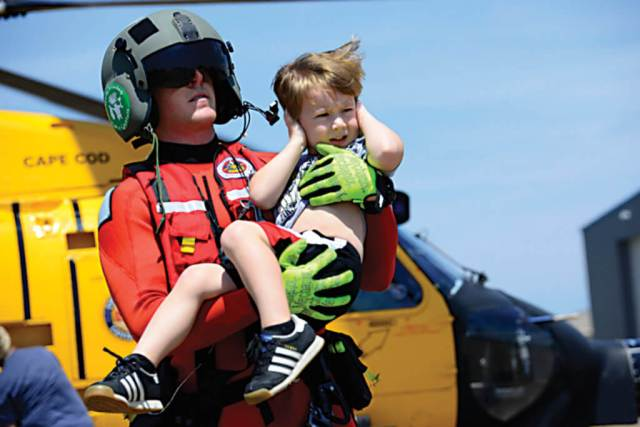 Coast Guard Petty Officer 3rd Class Evan Gallant, a rescue swimmer from Air Station Miami, carries a boy away from an MH-60 Jayhawk helicopter in Beaumont, Texas on Aug. 31. An aircraft crew working out of Air Station Houston transported a group of people from a shelter to Jack Brooks Regional Airport in Beaumont. USCG Petty Officer 3rd Class Corinne Zilnicki Photo