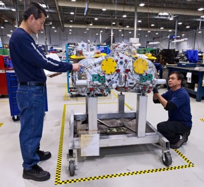 Two Vector technicians work on a helicopter engine. Vector Aerospace Photo