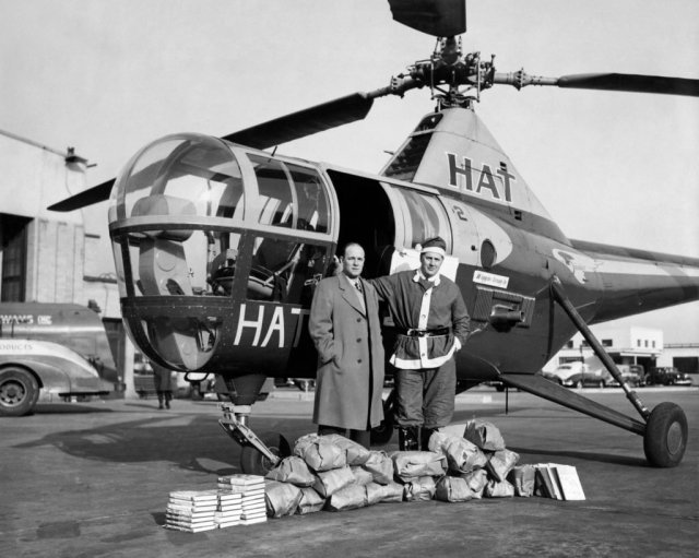 The program started out with fixed-wing aircraft in 1929; this changed in 1945 when a pilot tried to drop a doll out his plane for a little girl in Martha's Vineyard, and it broke on some rocks on the shore. A helicopter was chartered the following year so the doll could be hand-delivered to the girl. But helicopters were not brought in to the program on a permanent basis until 1981. Friends of Flying Santa Photo