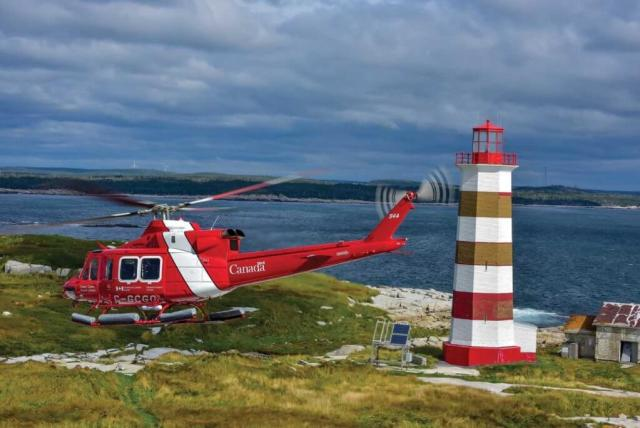 A Canadian Coast Guard Bell 412EPI holds a hover in front of a lighthouse off the coast of Halifax, Nova Scotia. The agency recently renewed its entire fleet of 22 aircraft. Mike Reyno Photo