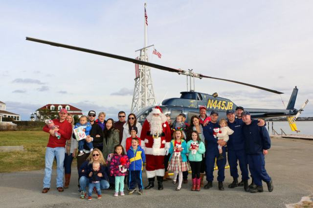 USCG families are gathered at Coast Guard Station Brant Point with Santa Claus, in front of a Bell 206B JetRanger III donated by JBI Helicopters. Friends of Flying Santa Photo