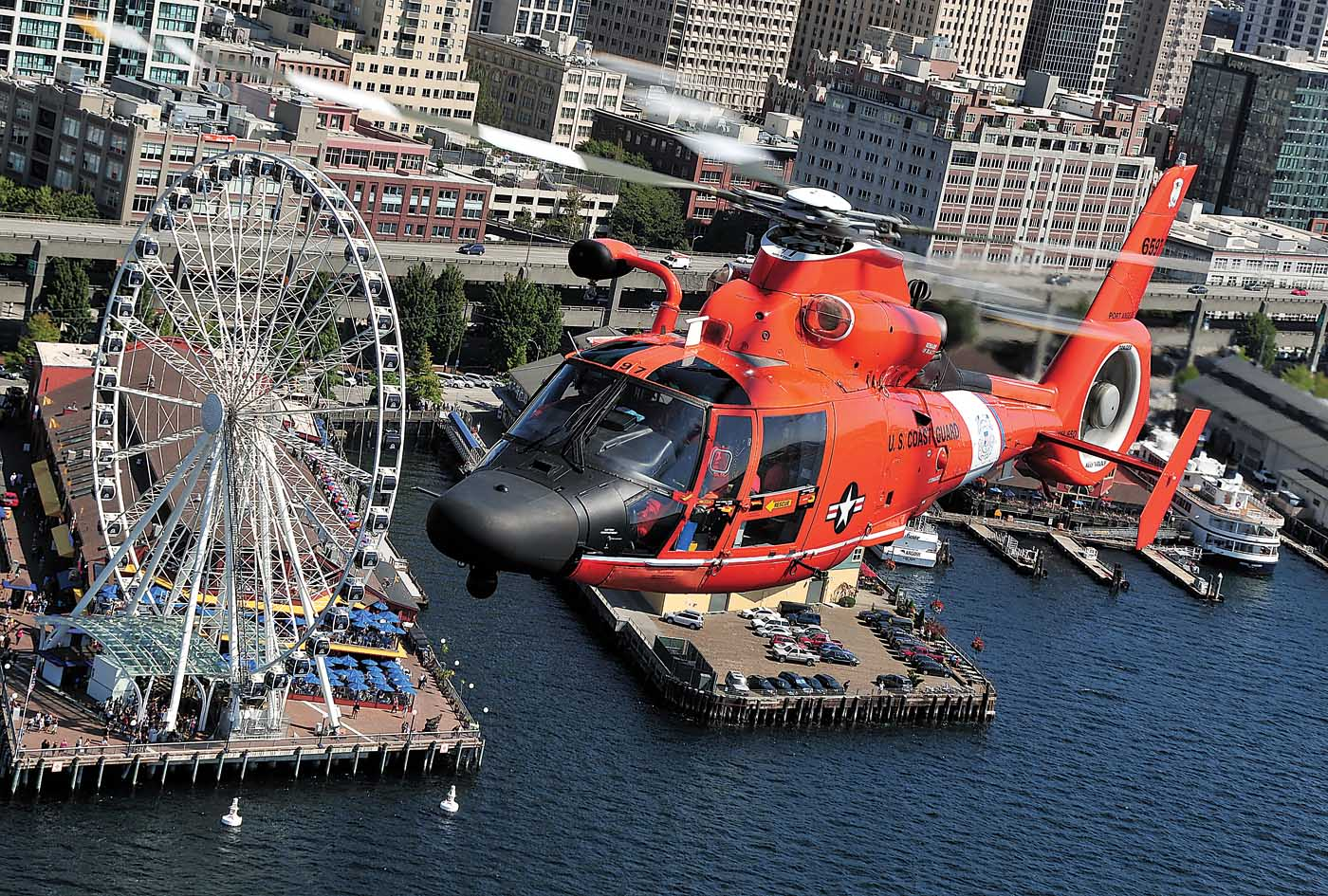 The operational area for U.S. Coast Guard Air Station Port Angeles includes Seattle's waterfront and harbor facilities. Here, an Airbus MH-65D flies past Seattle's Bay Pavilion. Skip Robinson Photo