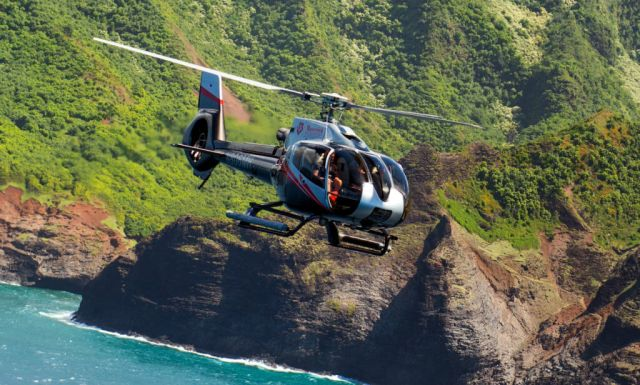 A Maverick Helicopters Airbus EC130 B4 flies along the Hawaiin coastline. Maverick Helicopters Photo