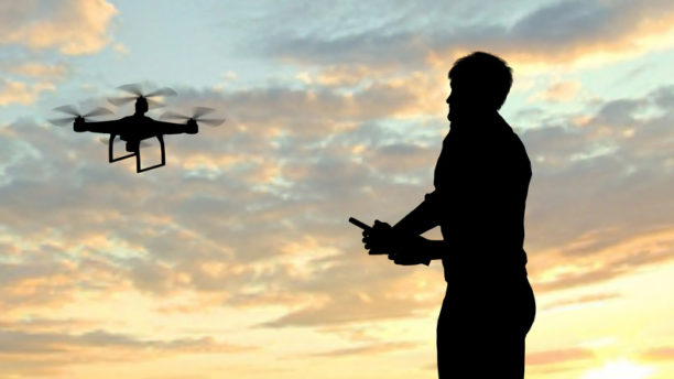 man operating of flying drone quadrocopter at sunset.