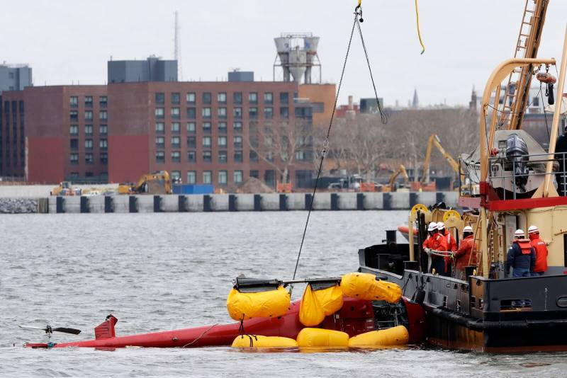 A Liberty Helicopters Airbus AS350 B2 is hoisted out of the East River on March 12.