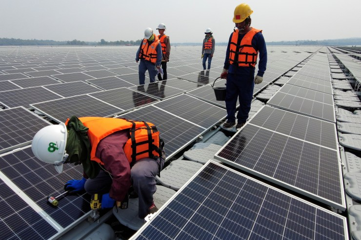 A worker kneels by one of the solar cell panels over the water surface of Sirindhorn Dam in Ubon Ratchathani, Thailand April 8, 2021. Picture taken April 8, 2021 with a drone. REUTERS/Prapan Chankaew - RC2HZM9ALEUC