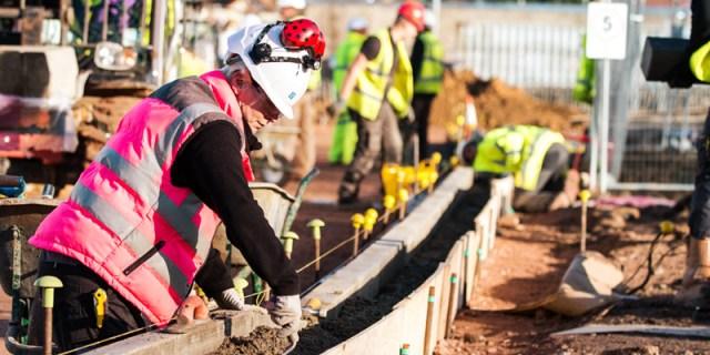 Une femme travaille avec des hommes sur le chantier de construction de la filiale à Chelmsford