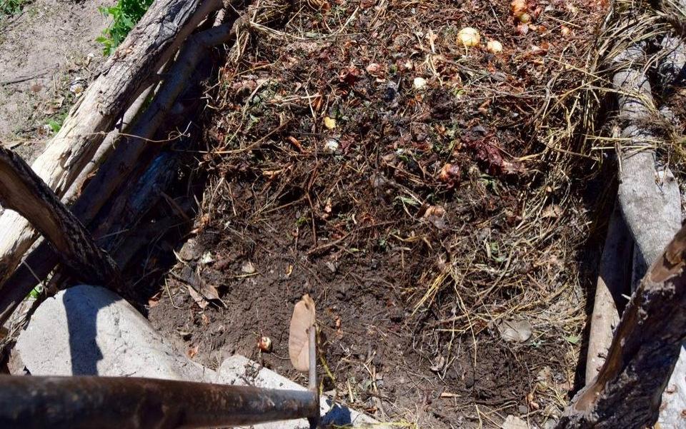 Kompostbeholderen med indhold som begynder at ligne muld