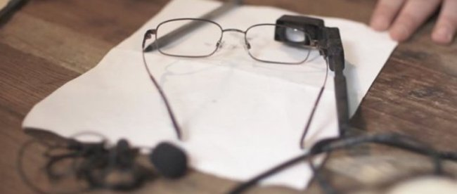 photo of live time closed captioning system - pair of glasses with an attached camera resting on a table