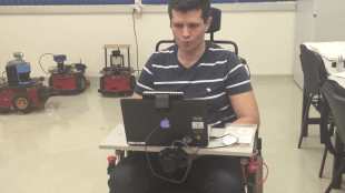 "a person making the ""kiss"" facial expression to maneuver wheelie the wheelchair"