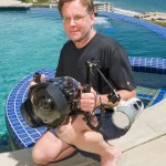 Photo of Bruce Hall by a swimming pool. He is holding a camera in his hand.
