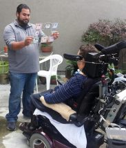 an interpreter displaying the e-tran board to a person in a wheelchair.