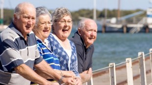 a group of four seniors standing near a lake, looking at something and laughing.
