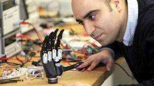 a man looking closely at the intuitive hand. It is seen resting on a desk with lots of cables in the background.