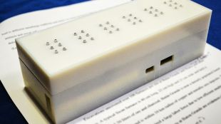 photo of current version of tactile placed on top of a book and displaying six characters in braille.