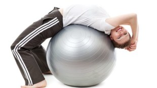 A young boy resting on an exercise ball
