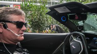 Sam Schimdt seen sitting in the driver seat of his car. A pipe that he pufs and sucks on to accelerate and brake the car is seen going into his mouth