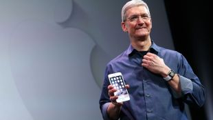 Tim Cook, CEO of Apple, seen holding an iphone in his right hand.