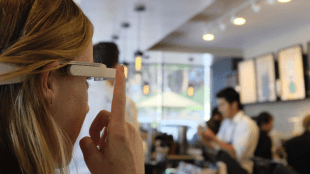 a woman in a coffees shop is seen pressing the button on her aira smartglasses.