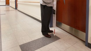 a blind person holding a white cane seen opening a door.