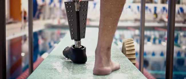 a person just about to get into a swimming pool seen wearing the fin prosthetic leg on his left side