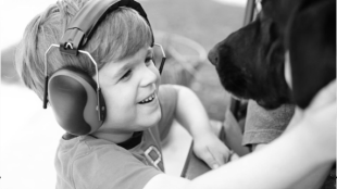 a young boy seen wearing headphones and playing with a dog