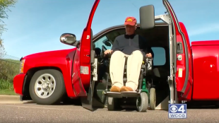 "Phil seen getting out of his truck in his wheelchair. His modified Silverado uses his ""KAS"" system that can lift and lower a vehicle completely to the ground and eliminates the need for a ramp to get in and out of the vehicle."