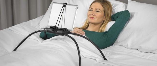 a woman using tablift with a tablet in bed
