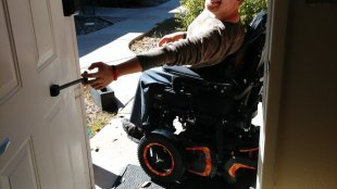 a man in a motorized wheelchair seen pulling on the t-pull door closer attached to a door.